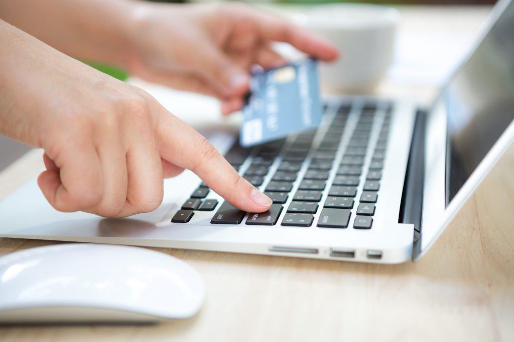 hand with credit card laptop