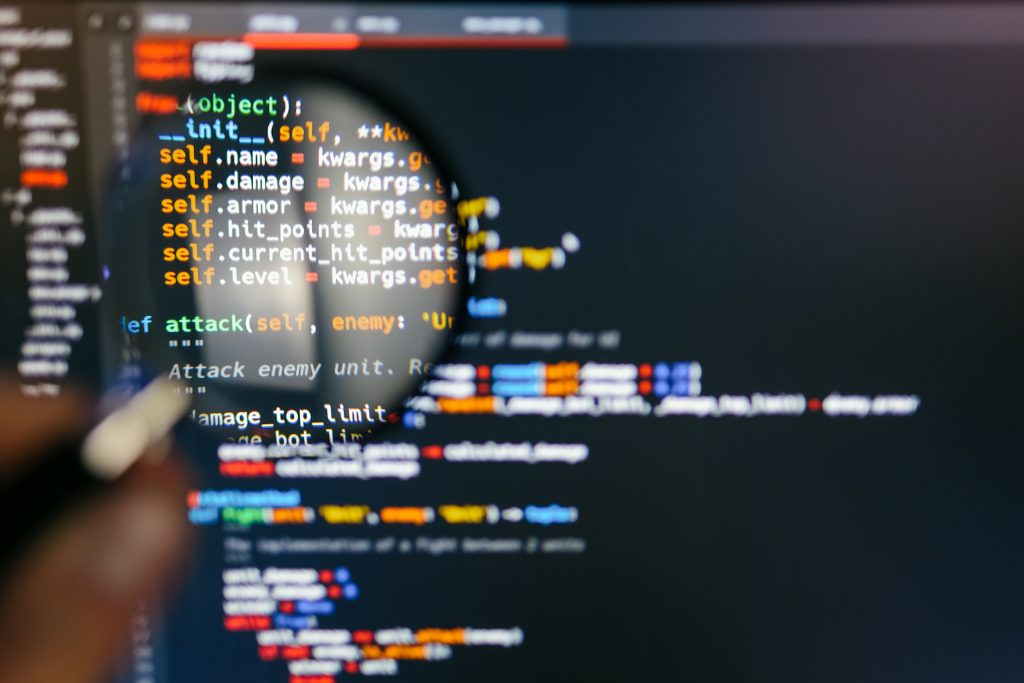 program code computer display magnifying glass close up